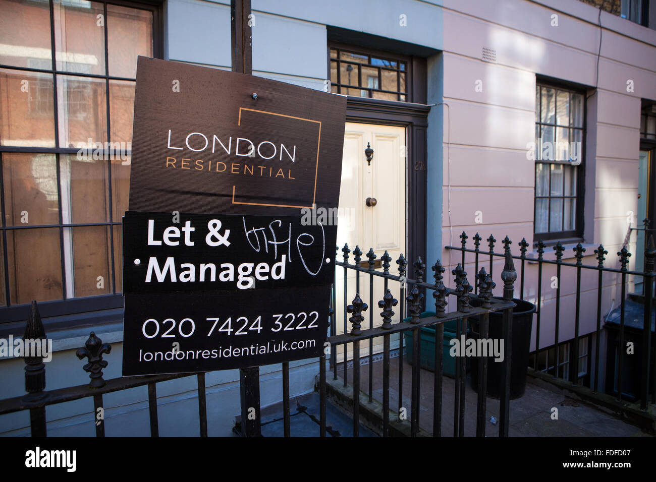 Let & Managed Estate Agent Sign outside terraced housing - Stock Image