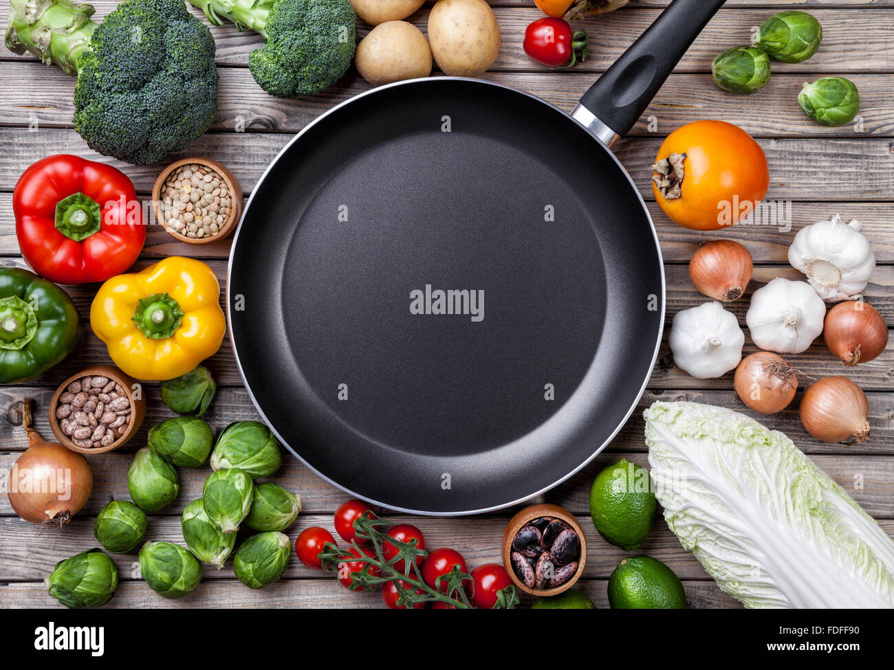Various vegetables fruits and herbs with a frying pan on wooden background - Stock Image