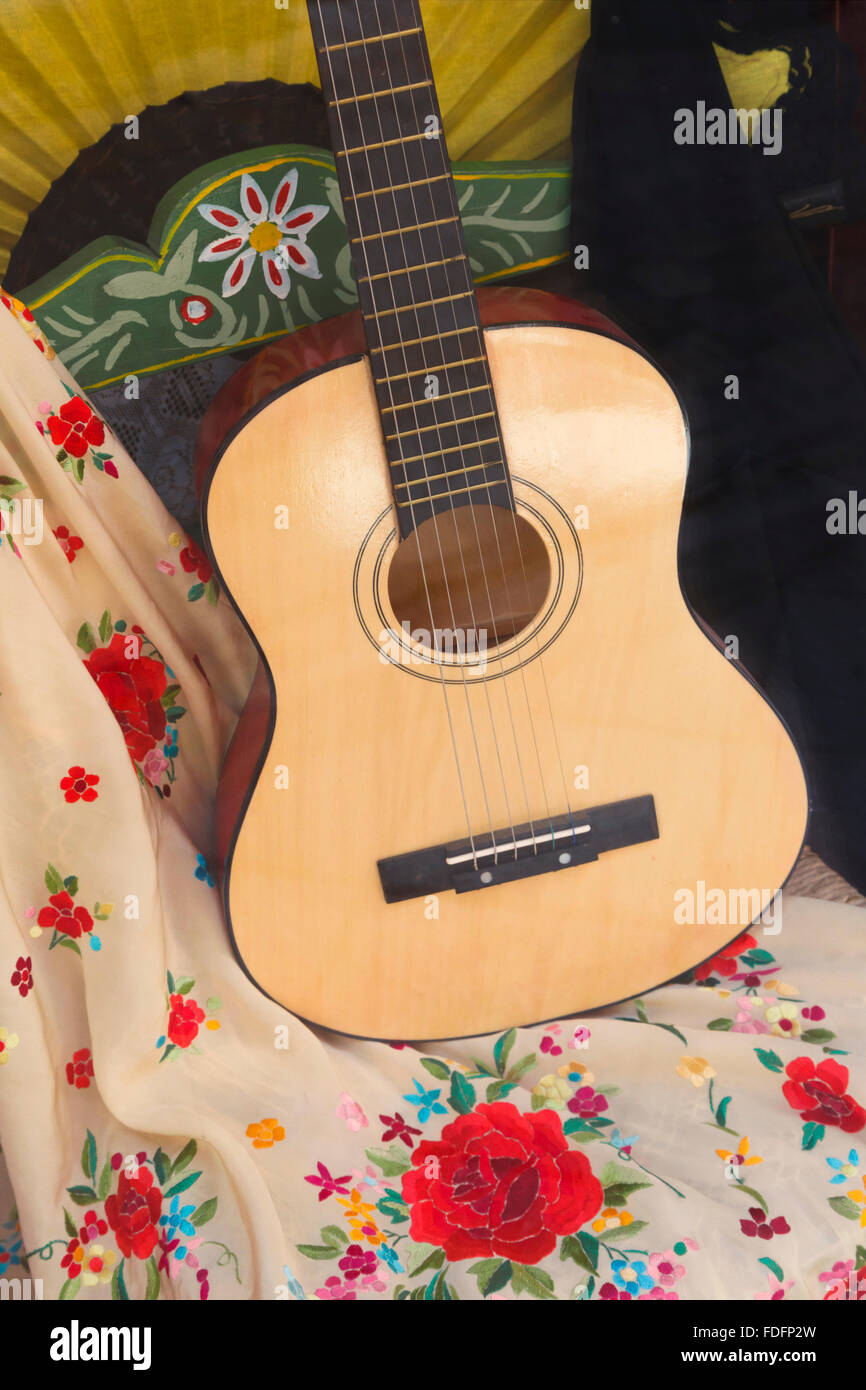 Spanish guitar resting on hand painted chair and Spanish shawl.  Andalusia, southern Spain. - Stock Image