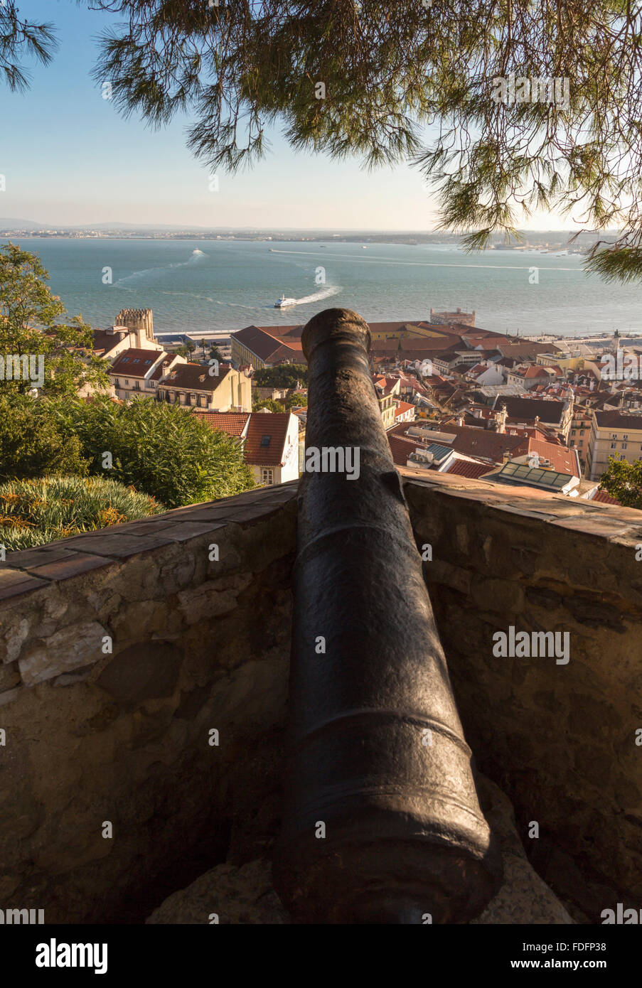 Lisbon, Portugal.  Cannon on the Castle of Saint George pointing towards boats crossing the Tejo river. - Stock Image