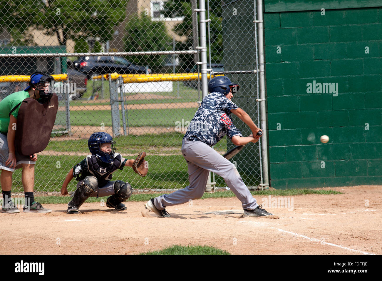 Batter swinging at ball in boys age 12 youth baseball game. St Paul Minnesota MN USA - Stock Image