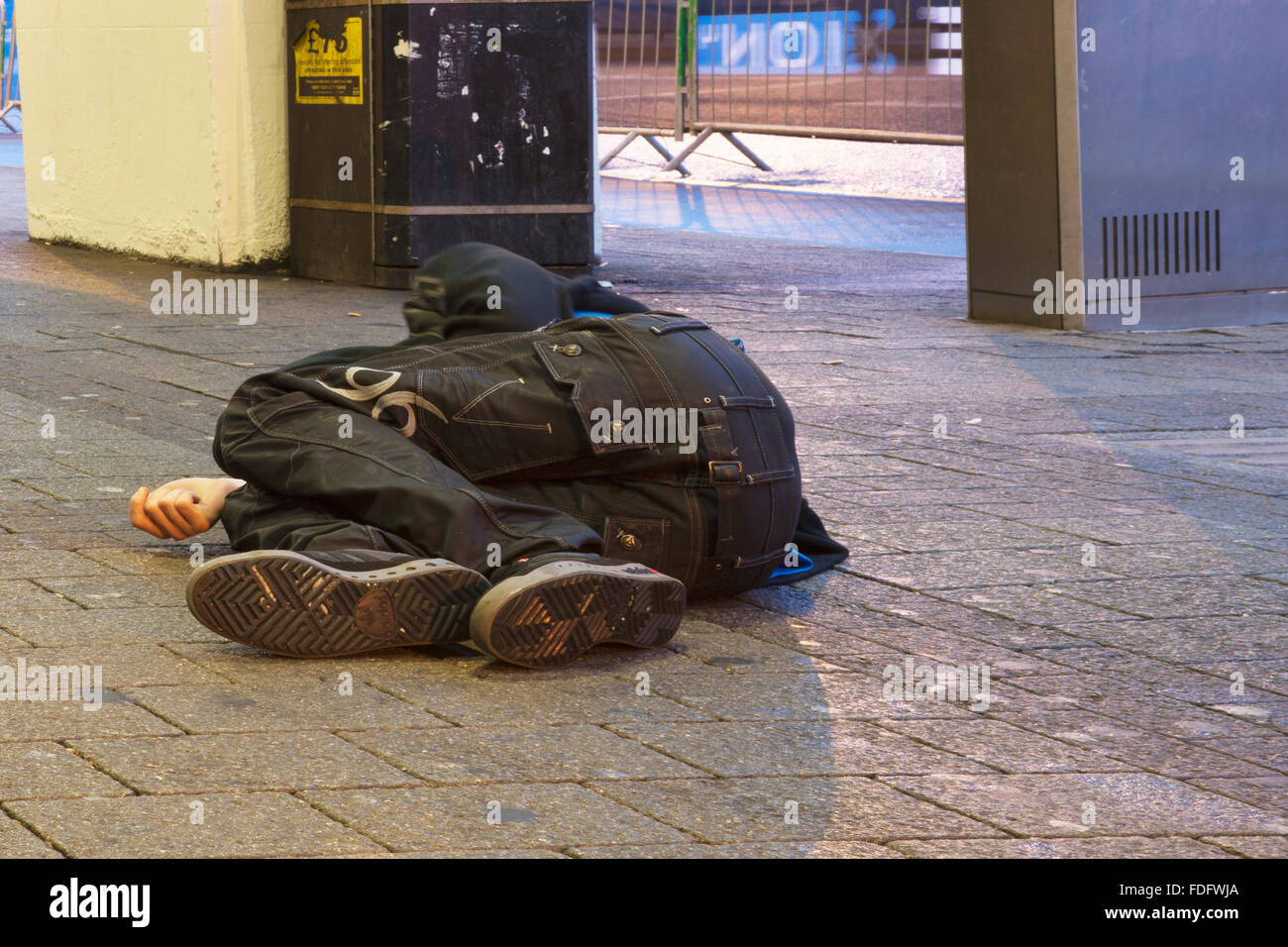 Homeless man sleeps on pavement in Sheffield - Stock Image