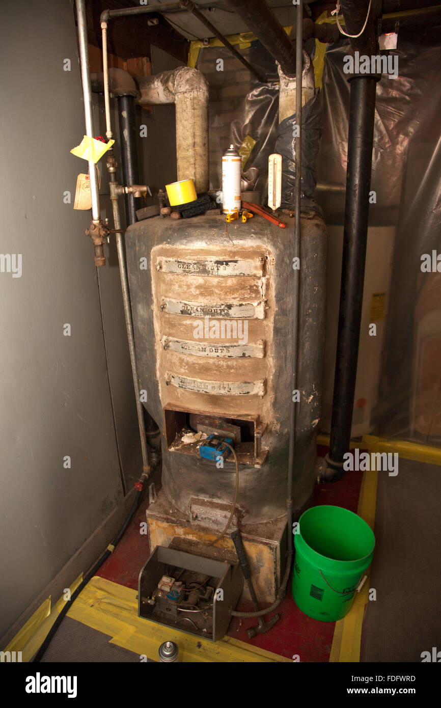 Old natural gas converted gravity hot water boiler about to be replaced with a modern furnace. St Paul Minnesota - Stock Image