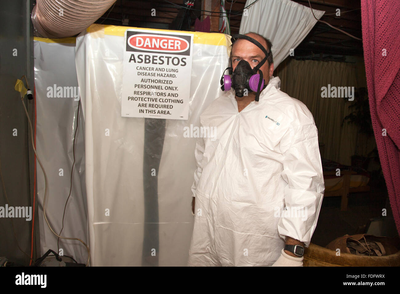 Workman in protective mask and body suit ready to remove asbestos insulation from an old furnace. St Paul Minnesota - Stock Image