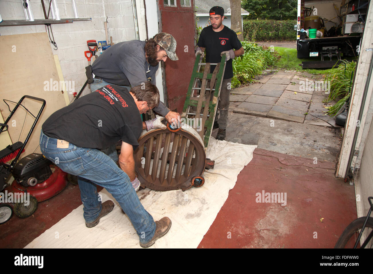 Placing very heavy section of old retired gravity furnace on dolly for removal. St Paul Minnesota MN USA - Stock Image