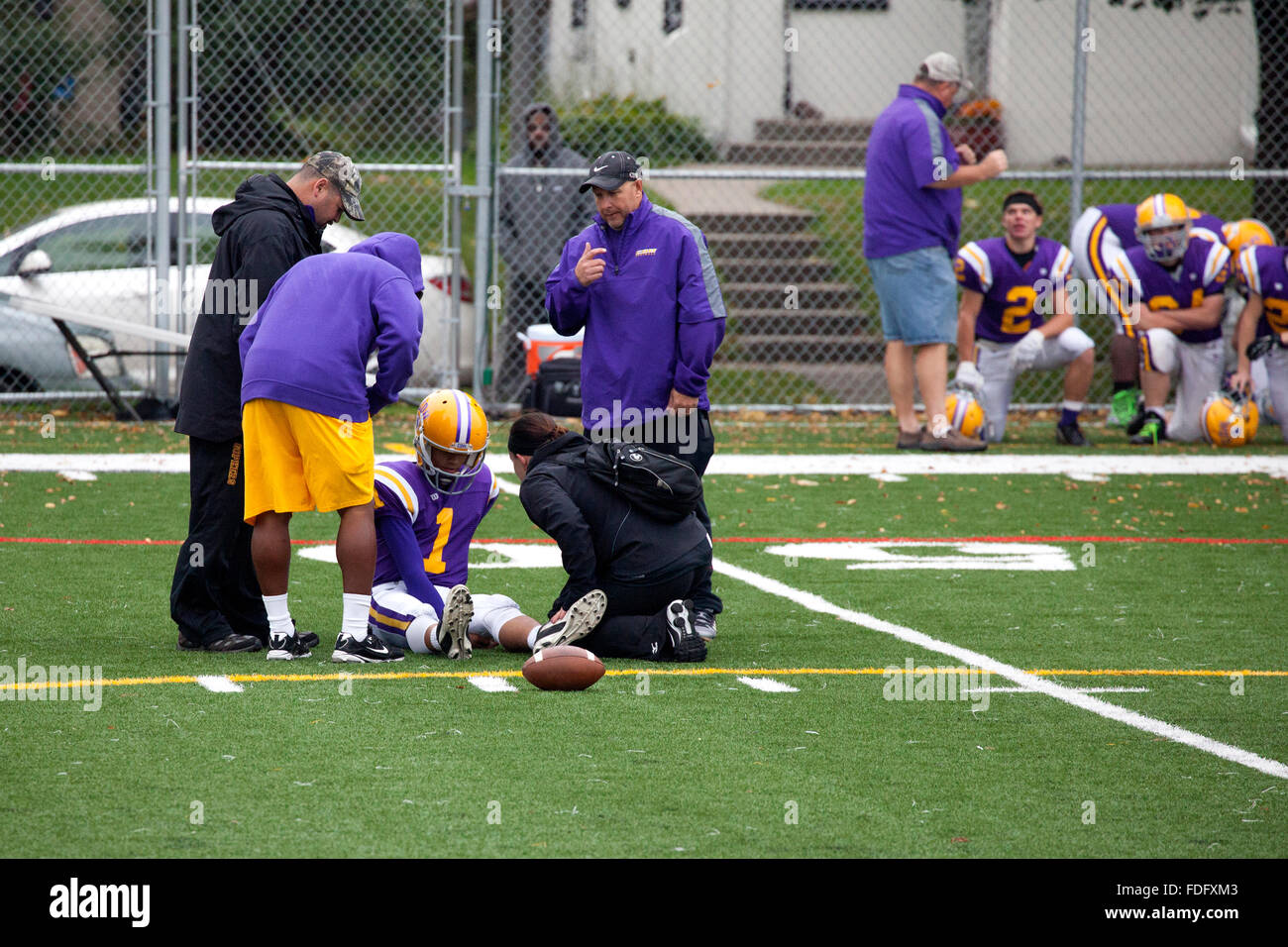 Trainers help injured Cretin-Derham Hall High School football player recover while sitting on ground. St Paul Minnesota - Stock Image