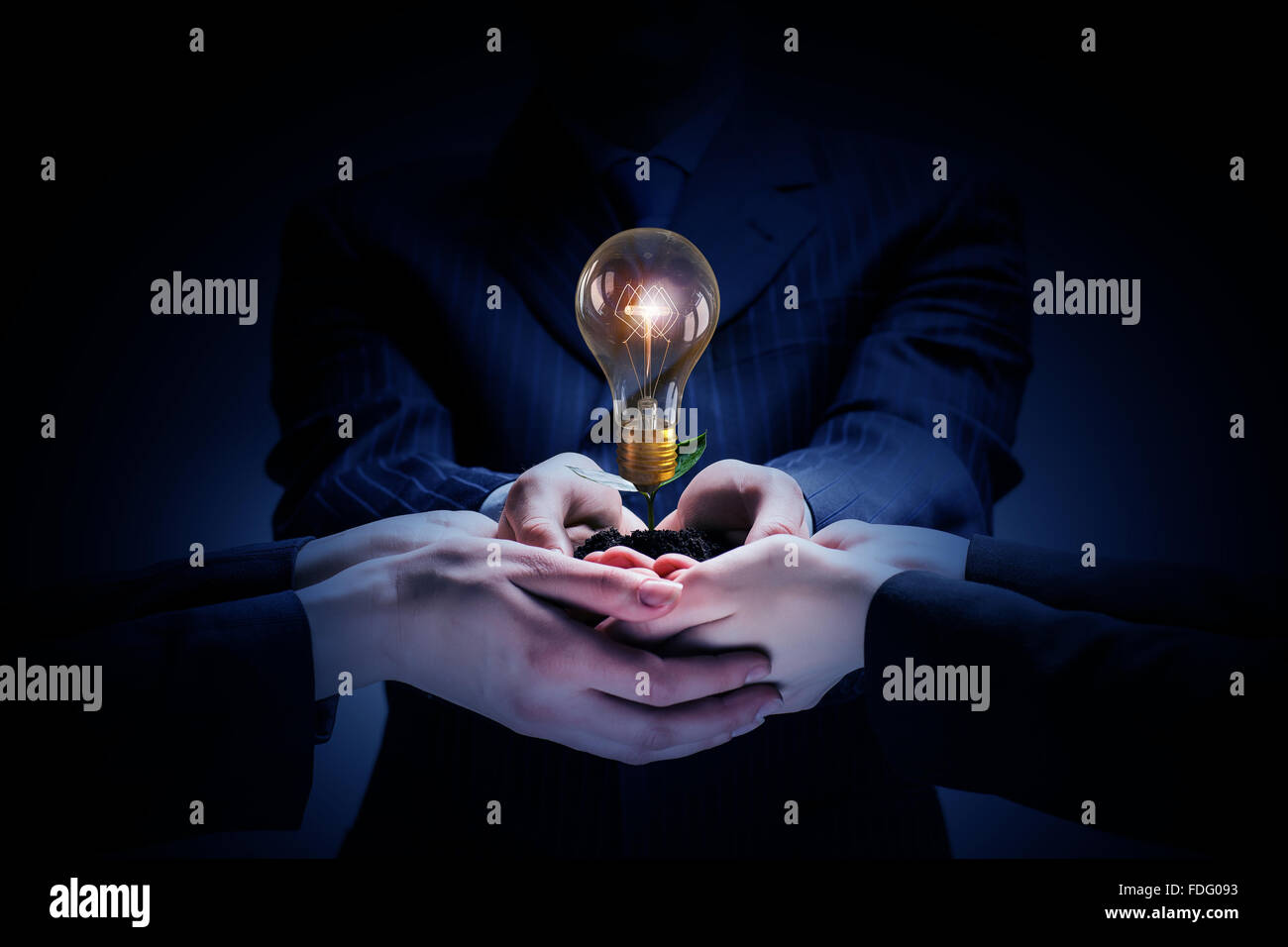 Brainstorming and teamwork concept with diverse business people holding light bulb in hands - Stock Image