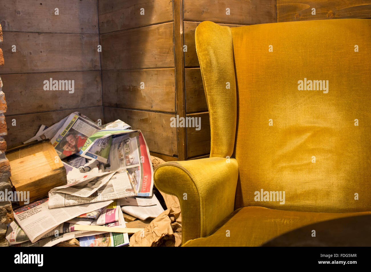 A comfy armchair and a pile of newspapers. - Stock Image