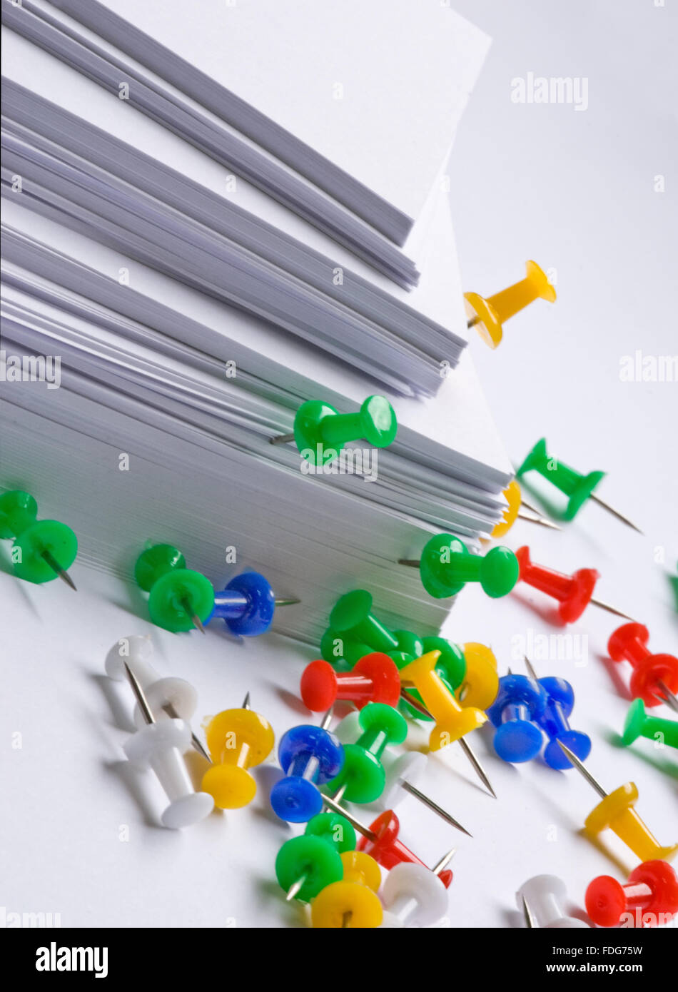 Office stationary with Colorful push pins and white note paper  sheets. - Stock Image