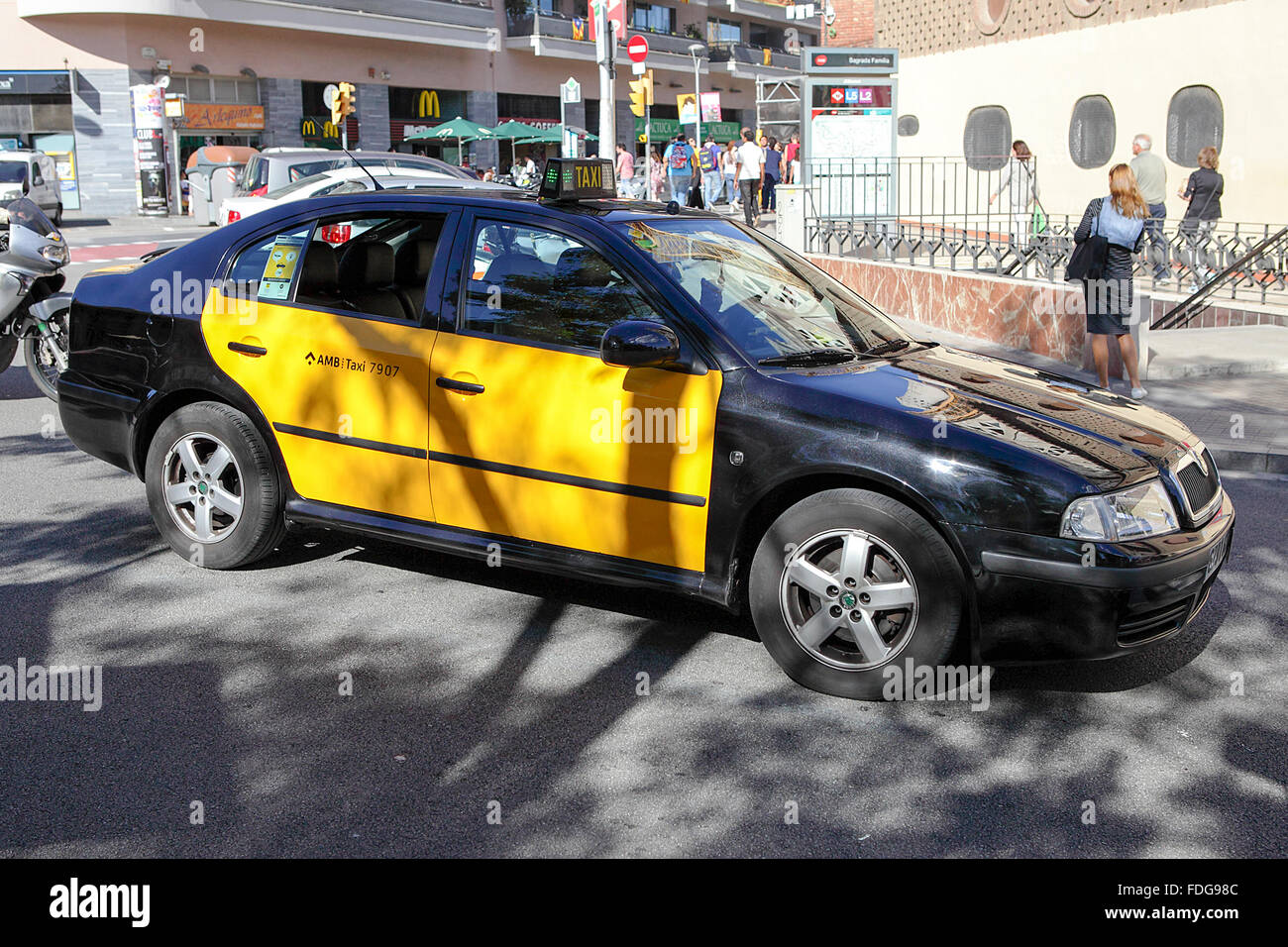 Black and yellow licensed taxi viewed here close to tourist hot spot Sagrada De Familia in Barcelona, Spain. - Stock Image