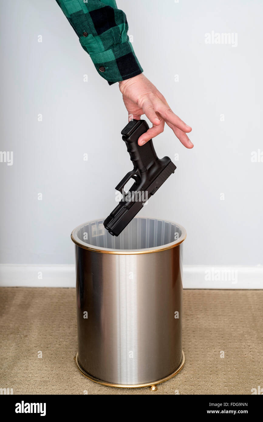 А man hand defiantly disgust , dislike throws the gun in the trash can - Stock Image