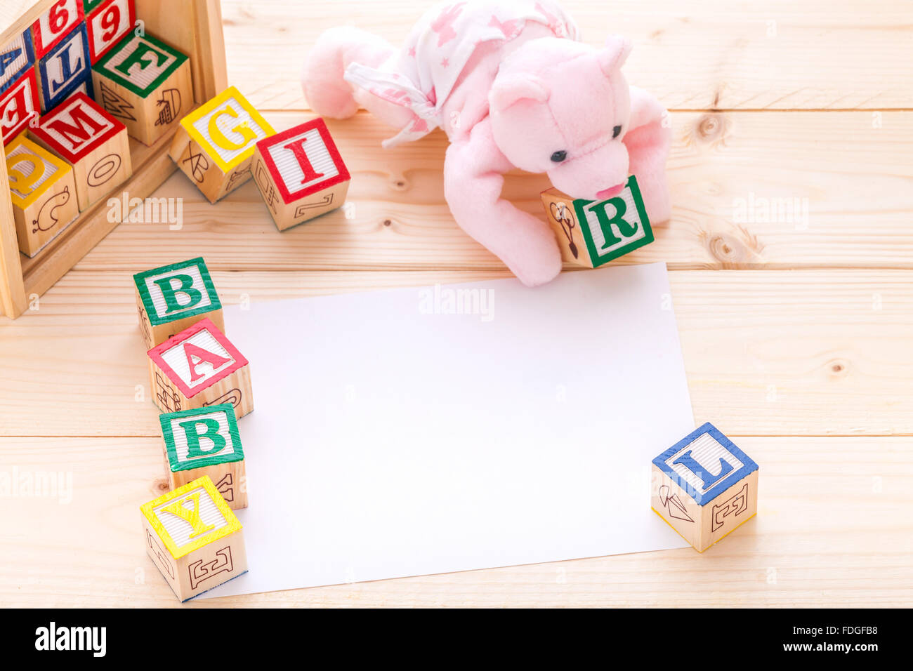 baby announcement invitation a pink toy bear spelling the words baby boy with wooden toy blocks on pine wood floor background