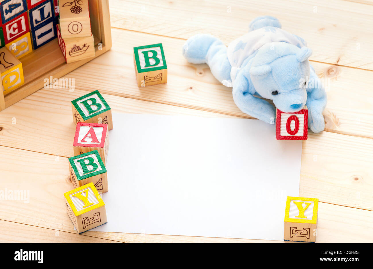 baby announcement invitation a blue toy bear spelling the words baby boy with wooden toy blocks on pine wood floor background
