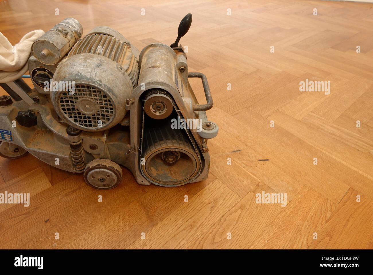 A grinding machine for wooden parquet floors on a oak parquet. - Stock Image