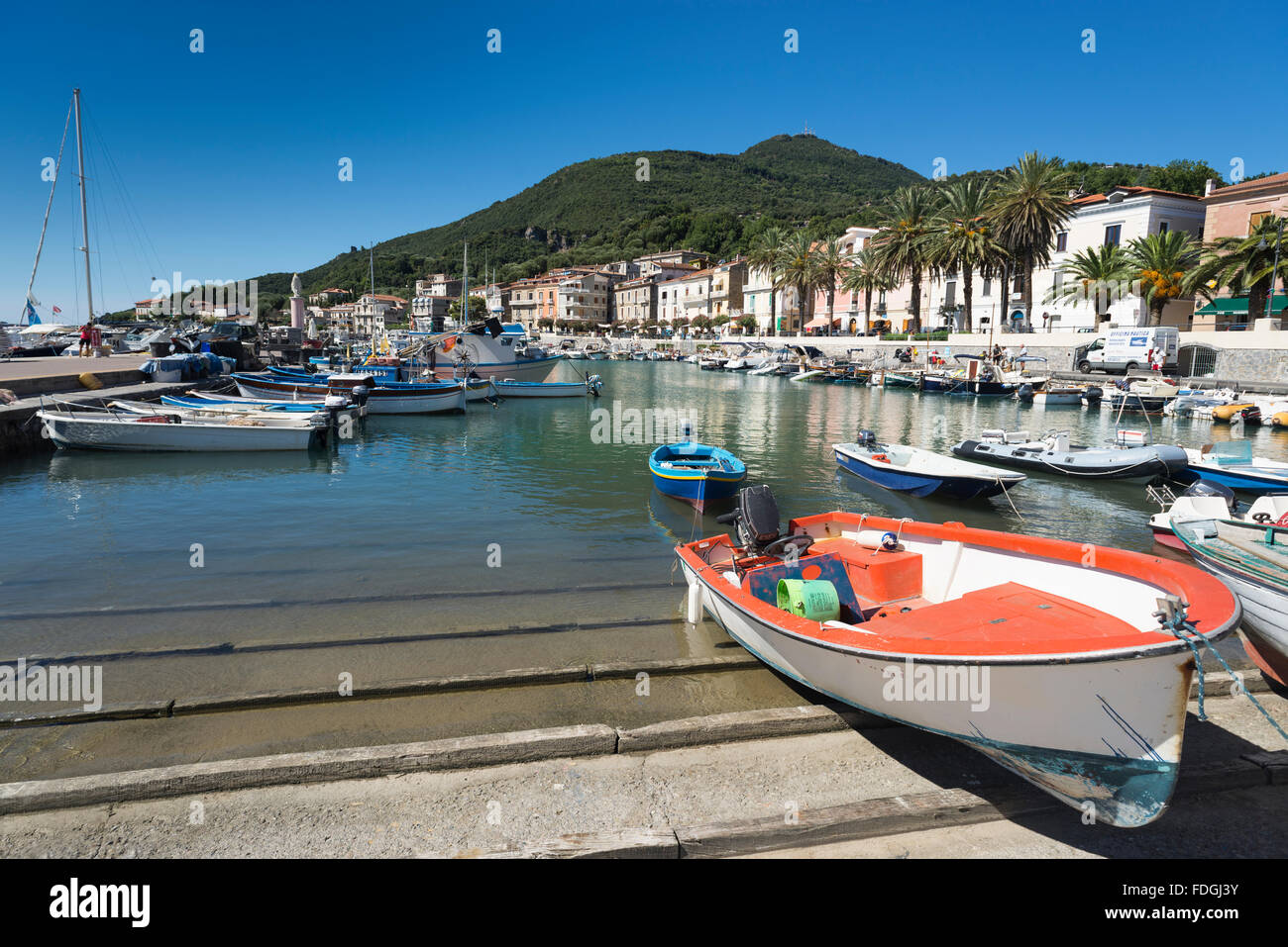 Fishing boats, motor boats and yachts in the picturesque harbor of Scario on the coast of the Mediterranean Sea - Stock Image