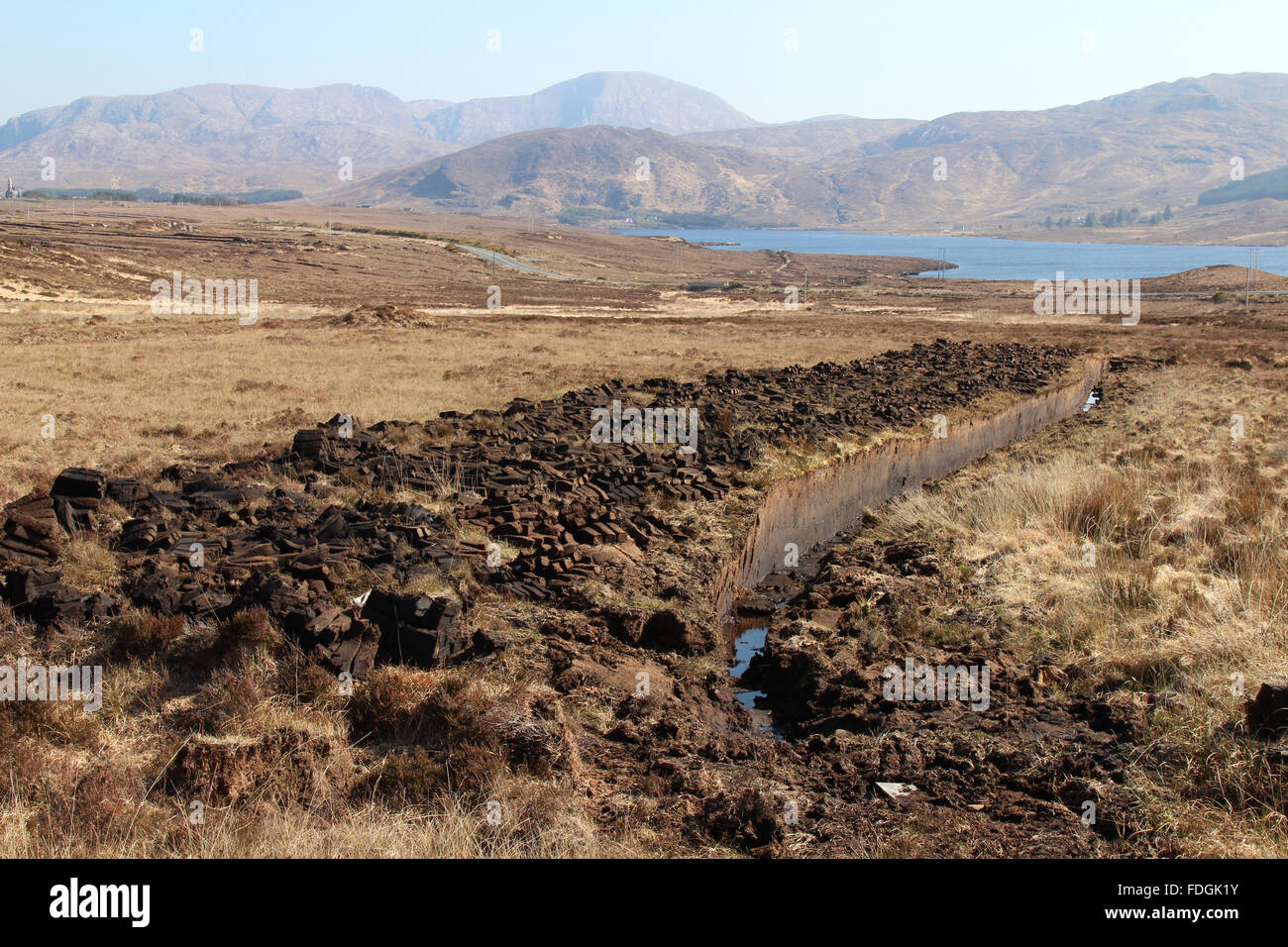 Peat bog and piles of cut turf drying in the sunshine.  County Donegal, Ireland. - Stock Image