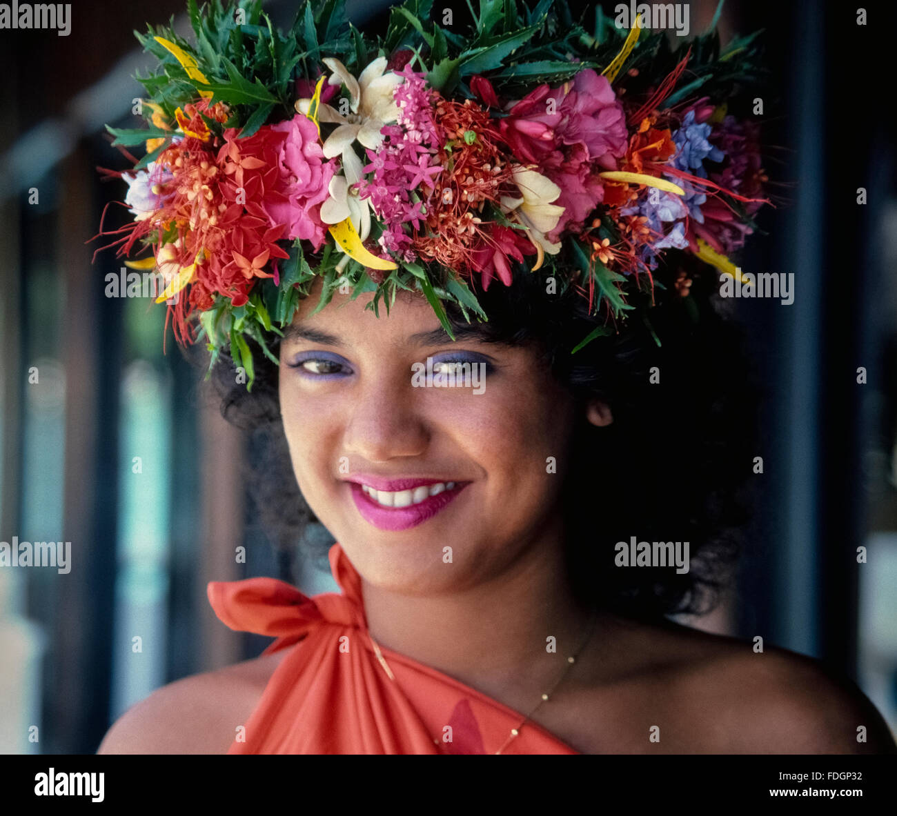 A traditional Tahitian floral crown adds to the beauty of this smiling girl on the island of Moorea in French Polynesia Stock Photo