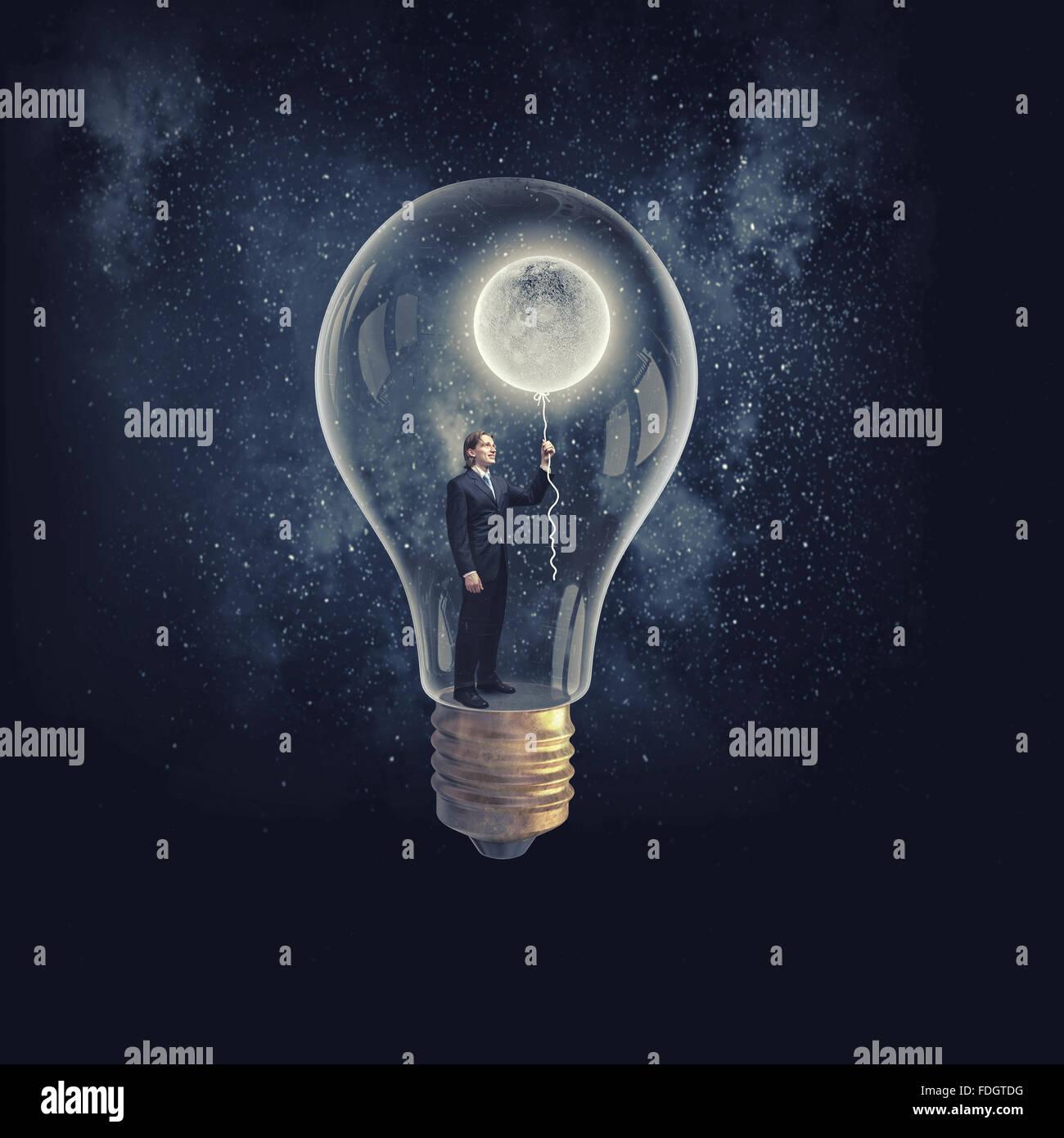 businessman inside of glass light bulb with moon balloon on dark