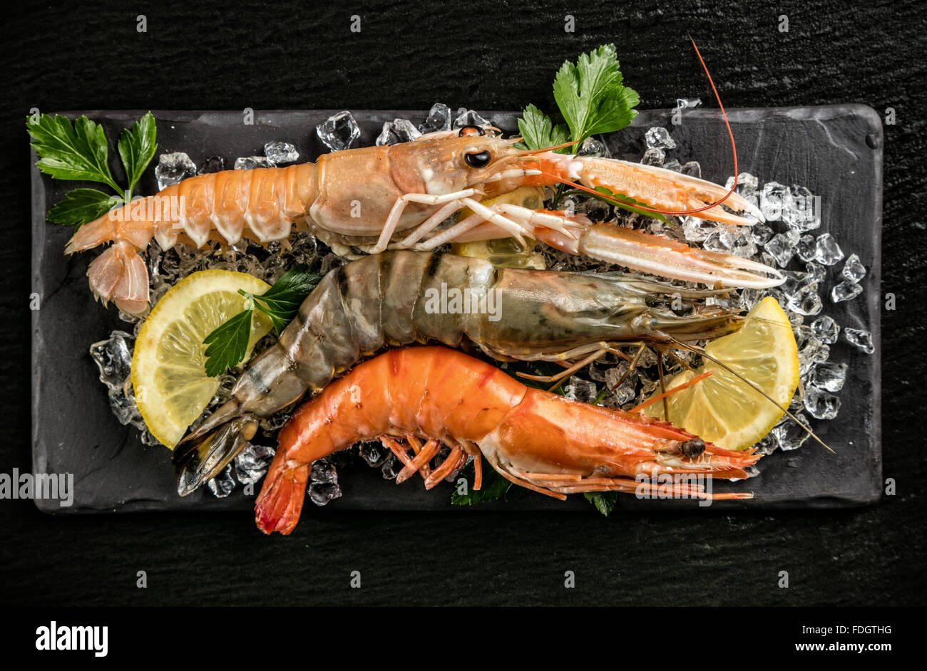 Prawns and lobster served on black stone - Stock Image