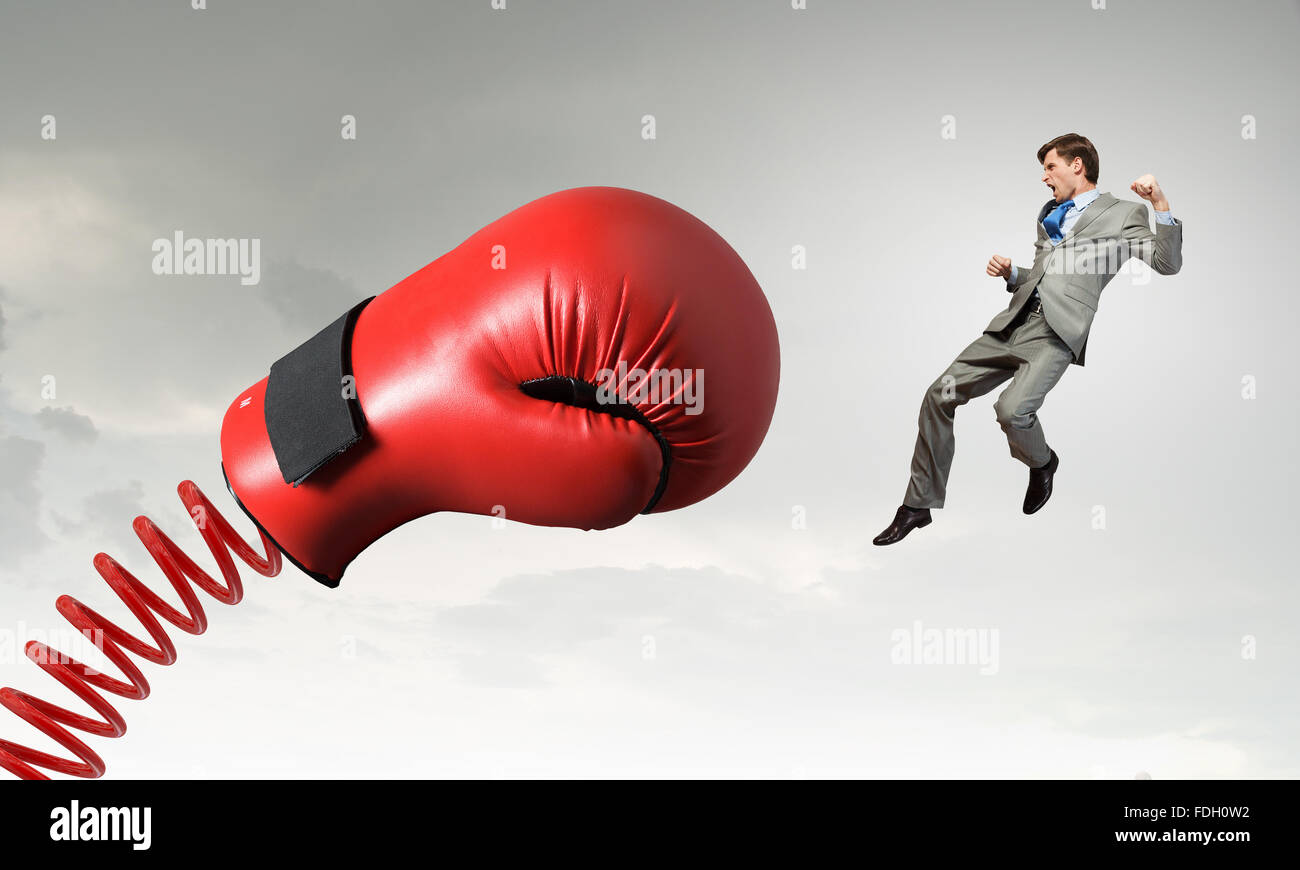 Young determined businessman fighting boxing glove on ...