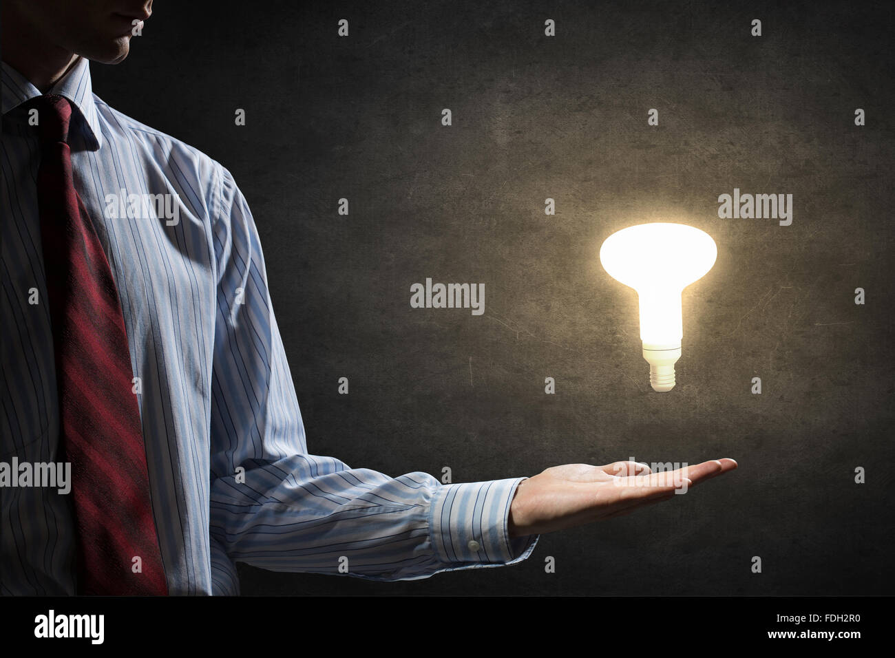 Businessman with illuminated glass light bulb in hand - Stock Image