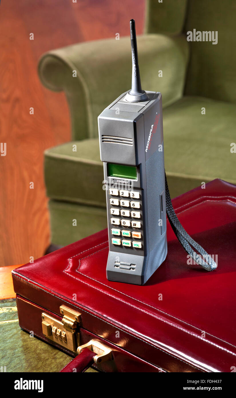 1987 first generation hand held mobile cell phone Mobira Cityman 1320 with 80's briefcase and chair - Stock Image