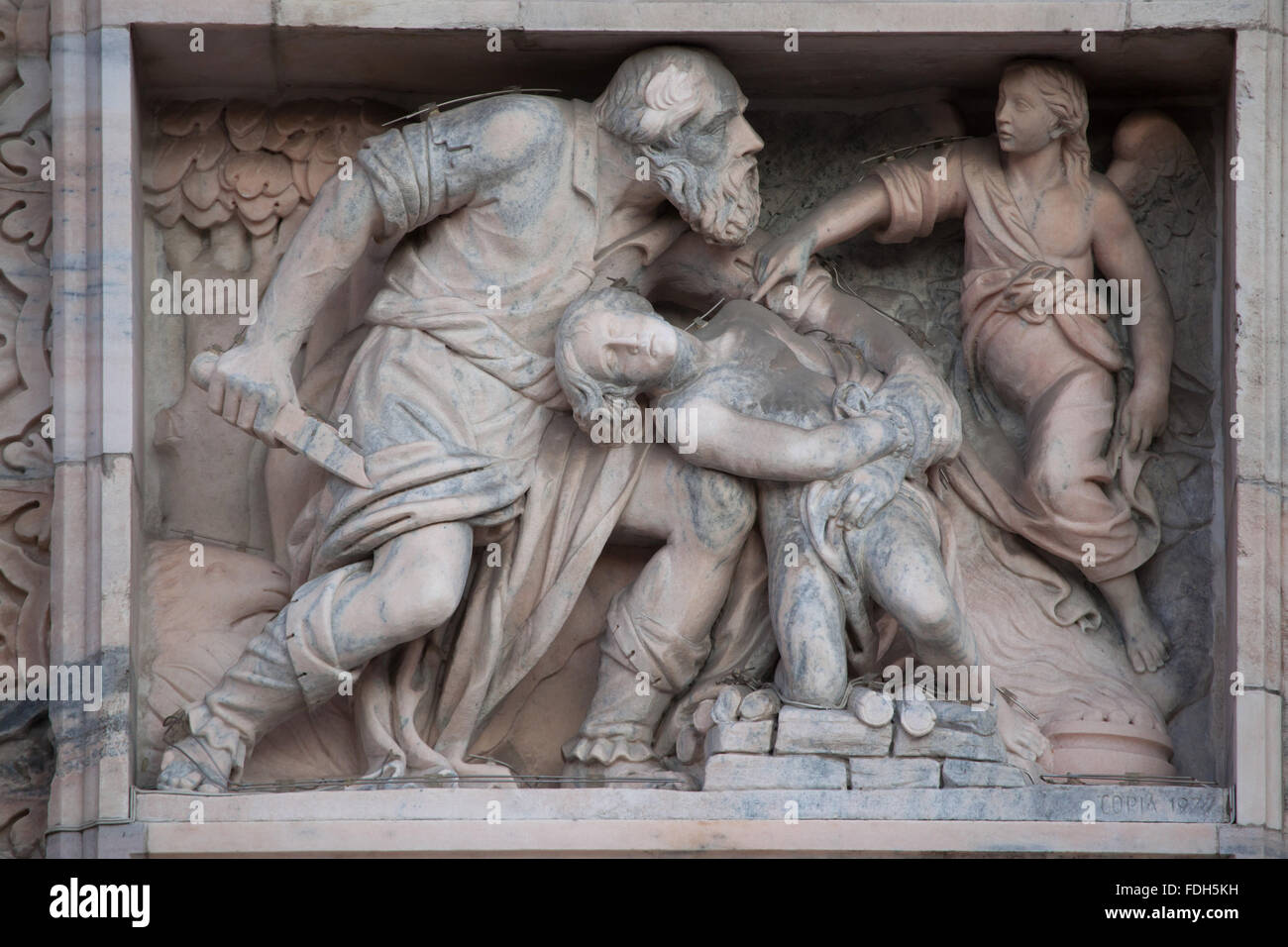 Sacrifice of Isaac. Marble relief by Italian sculptor Gaspare Vismara on the main facade of the Milan Cathedral - Stock Image