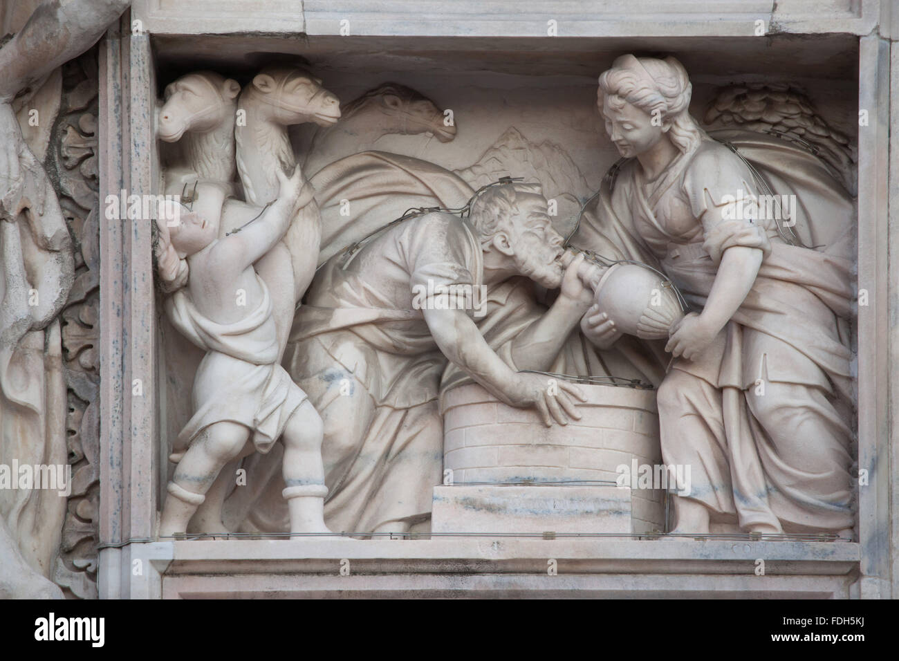 Rebecca at the well. Marble relief on the main facade of the Milan Cathedral (Duomo di Milano) in Milan, Lombardy, - Stock Image