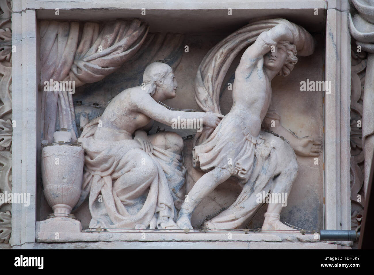 Joseph and Potiphar's wife. Marble relief on the south facade of the Milan Cathedral (Duomo di Milano) in Milan, - Stock Image