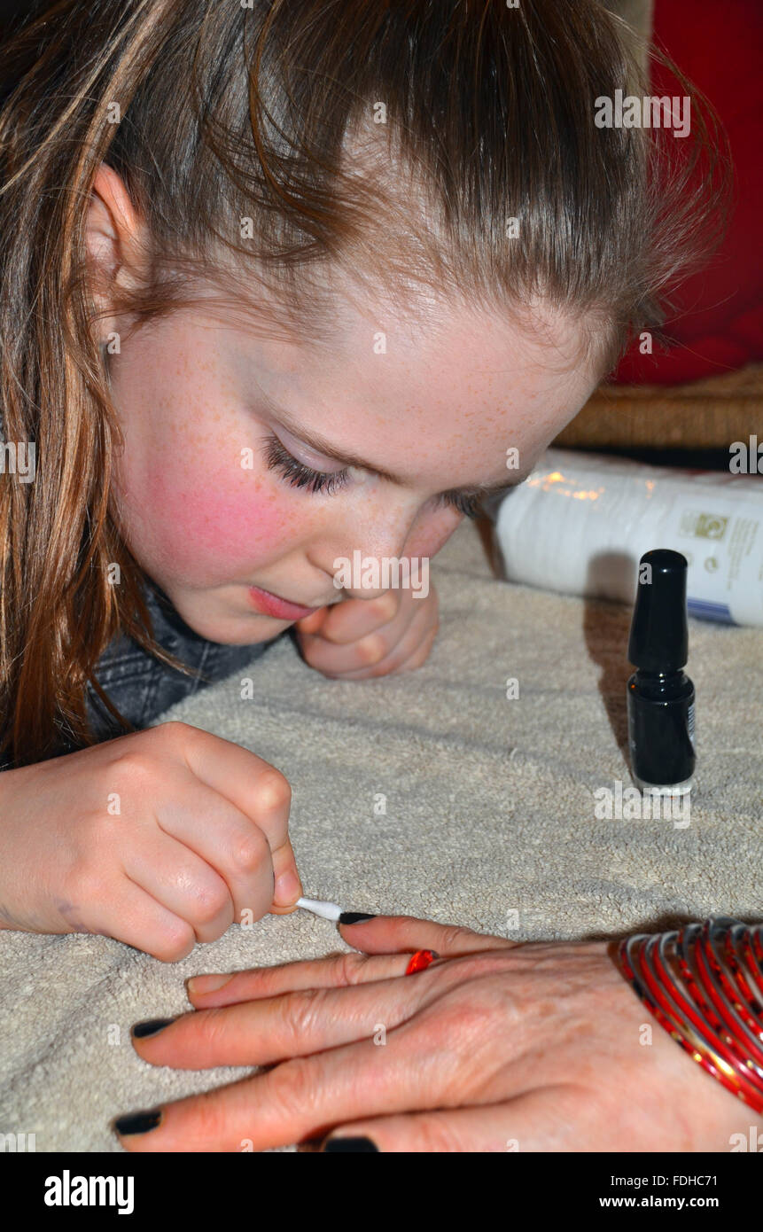 A young girl paints nail varnish onto a woman's fingernails. - Stock Image