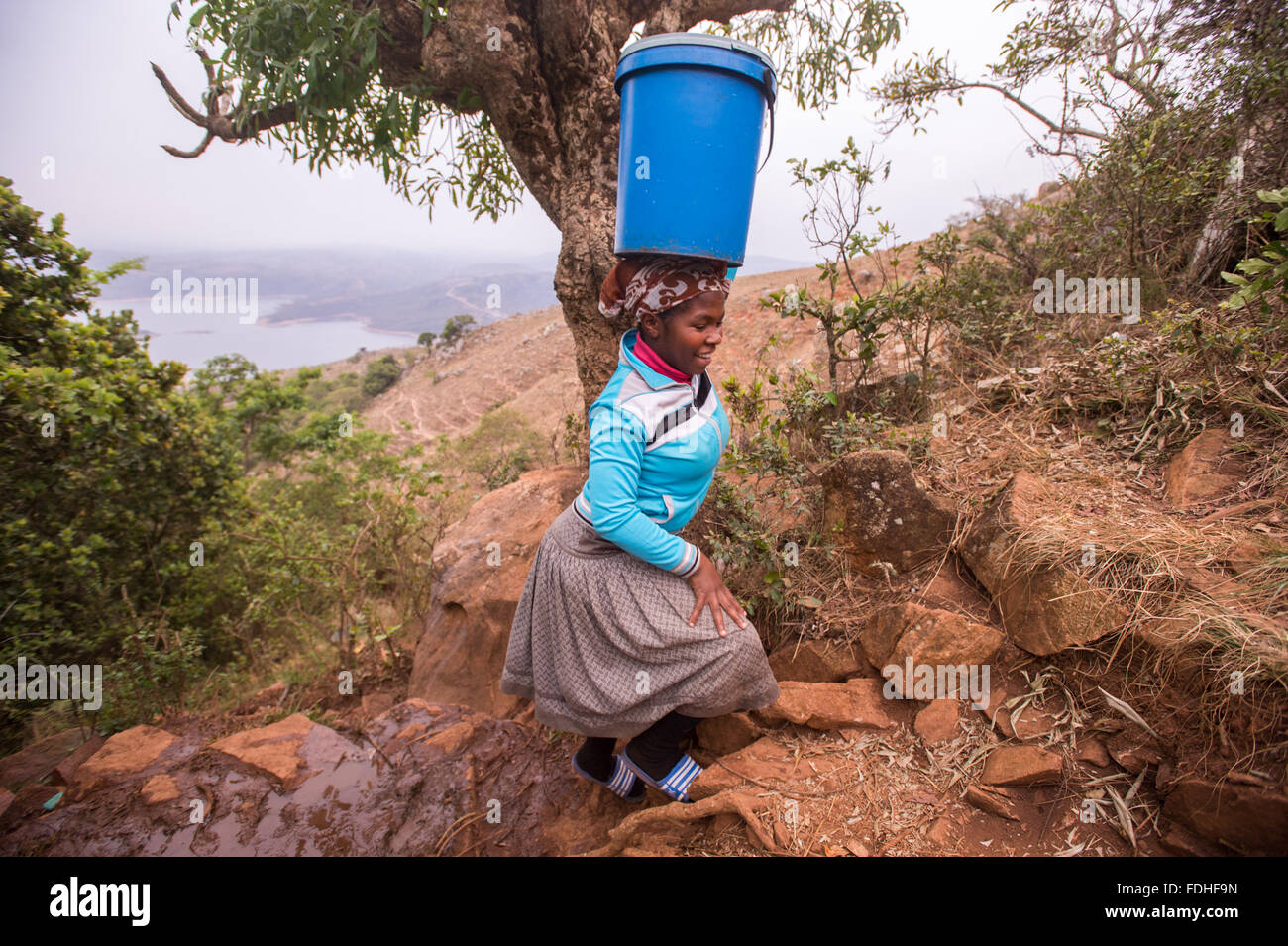 Woman carrying a bucket on her head over rocky terrain in the Hhohho region of Swaziland, Africa. - Stock Image