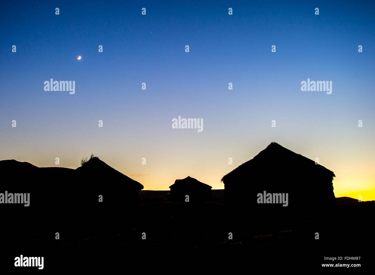 Silhouette of village huts in front of the sunset with the moon rising in Lesotho, Africa - Stock Image
