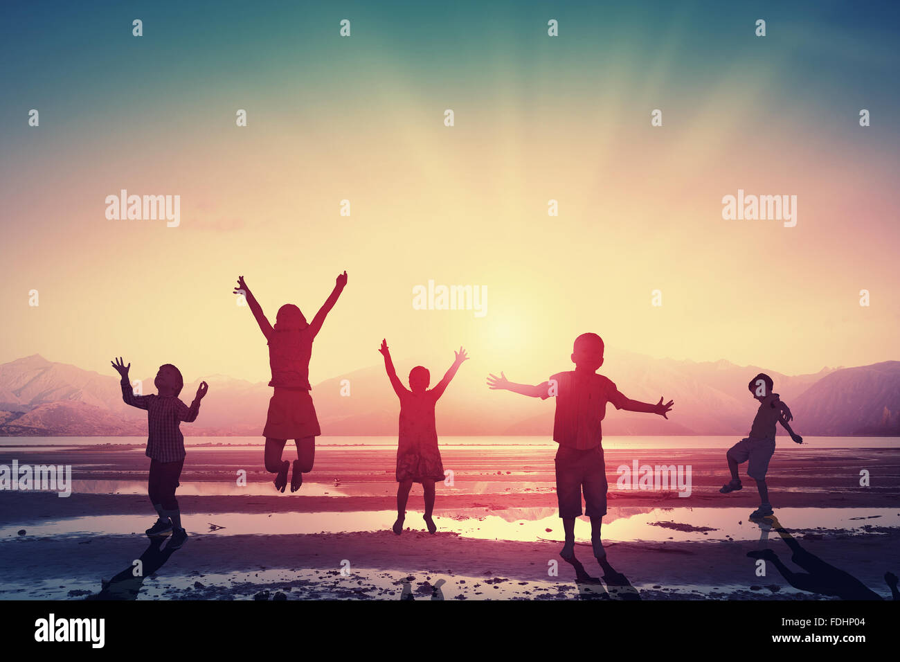 Silhouettes of group of children jumping high joyfully on sunset background - Stock Image