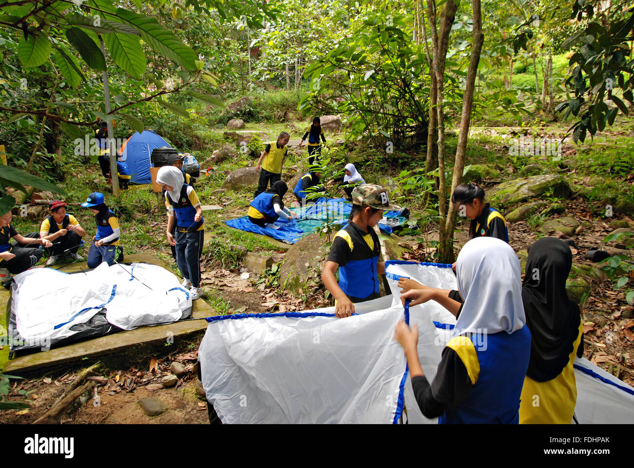 Kawang, Papar March 7, 2015 : A group of school girls working together pitching up tents for school extracurricular Stock Photo