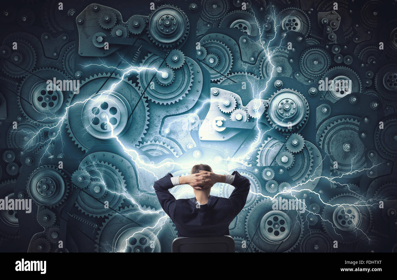 Young relaxed businessman sitting in chair and looking at gears mechanism - Stock Image