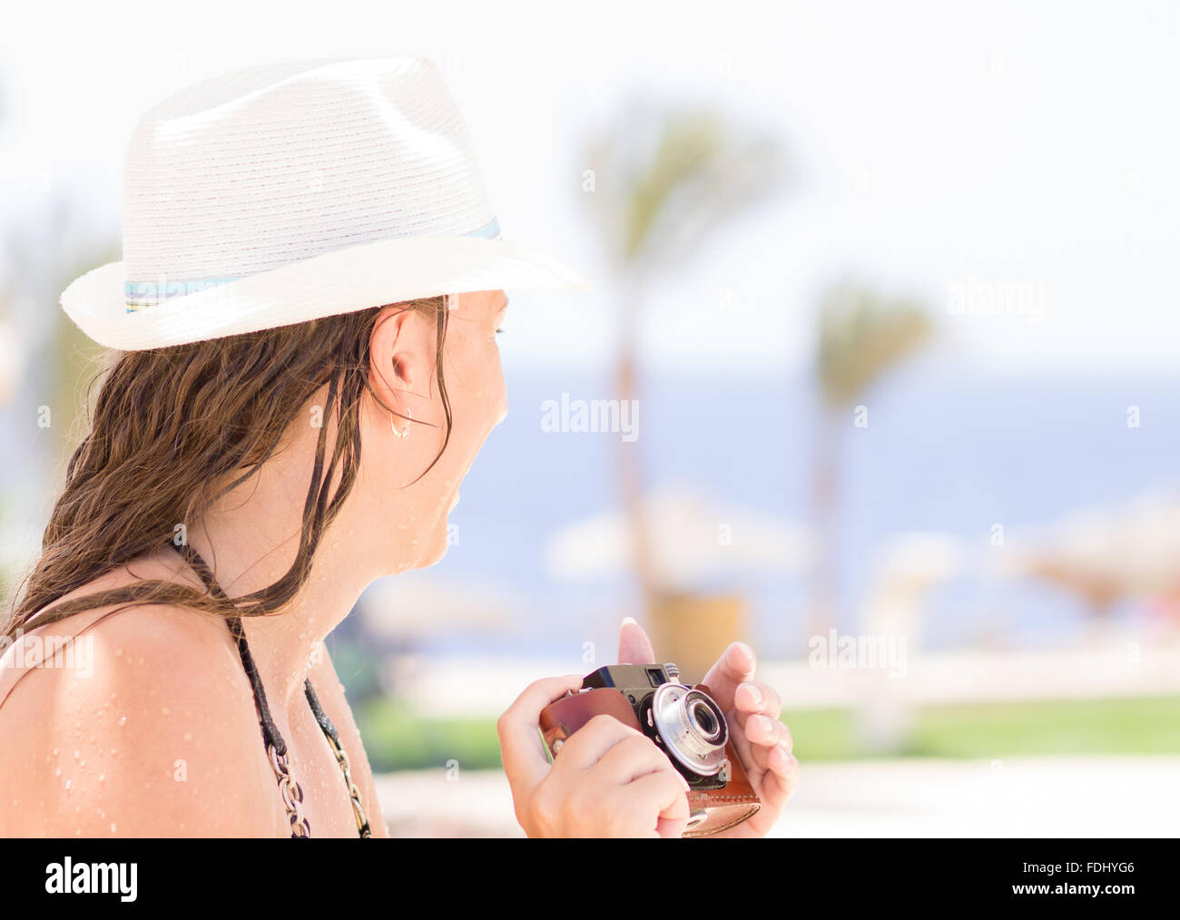 Young girl taking photos with old film camera on summer vacation. Holidays tourism background - Stock Image