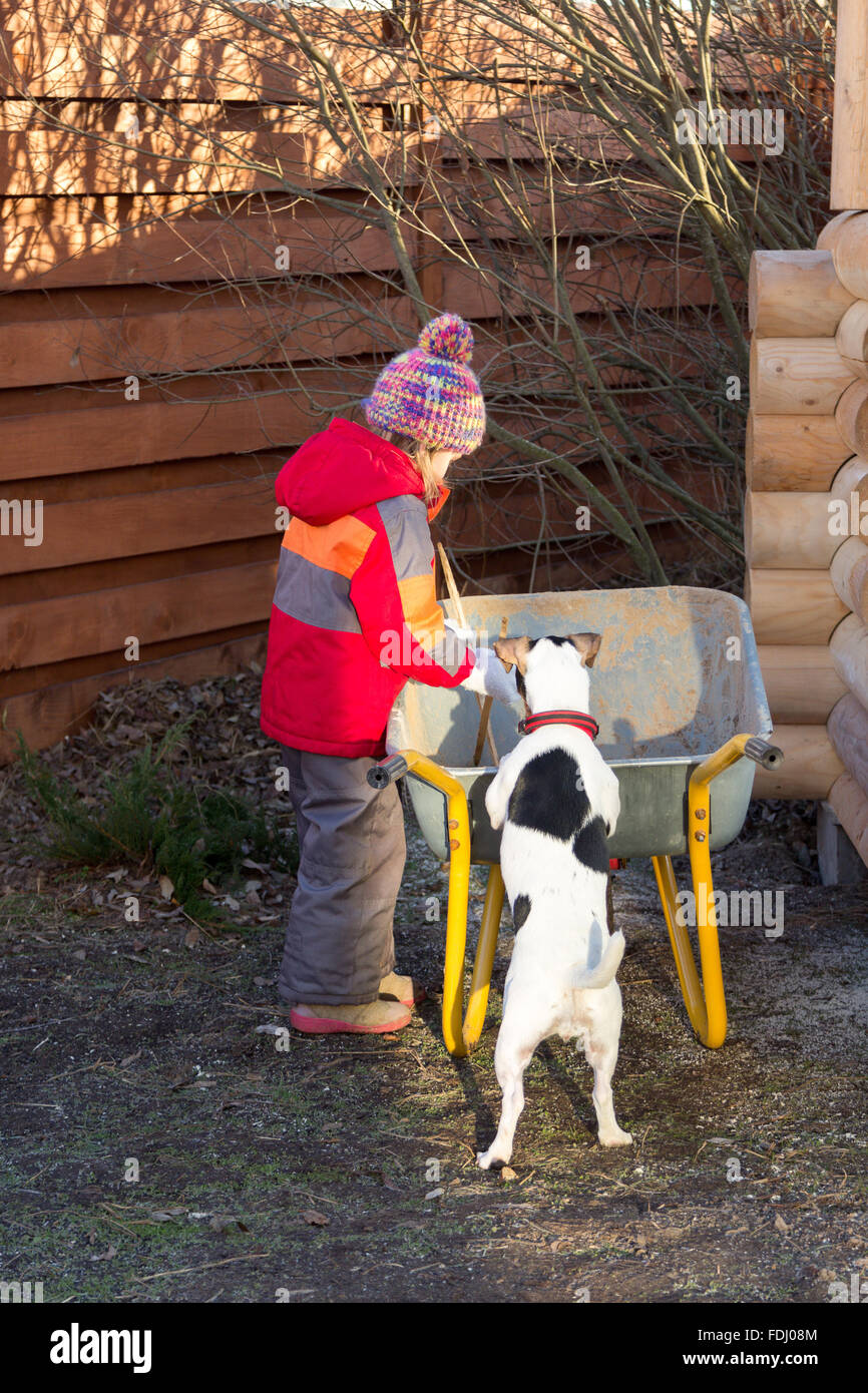 little girl with a dog looking at something in a wheelbarrow - Stock Image