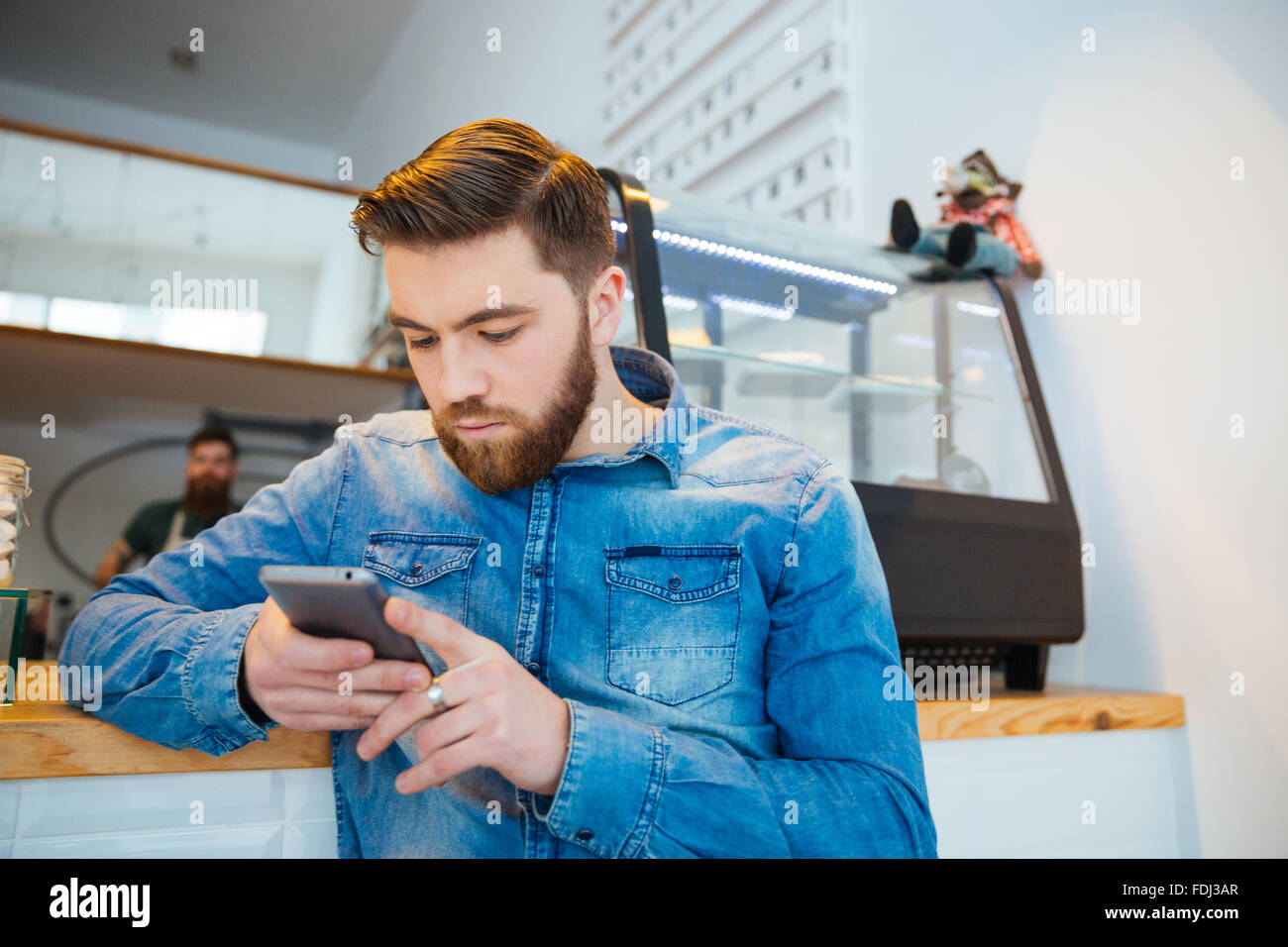 Handsome young man using smartphone in cafe Stock Photo