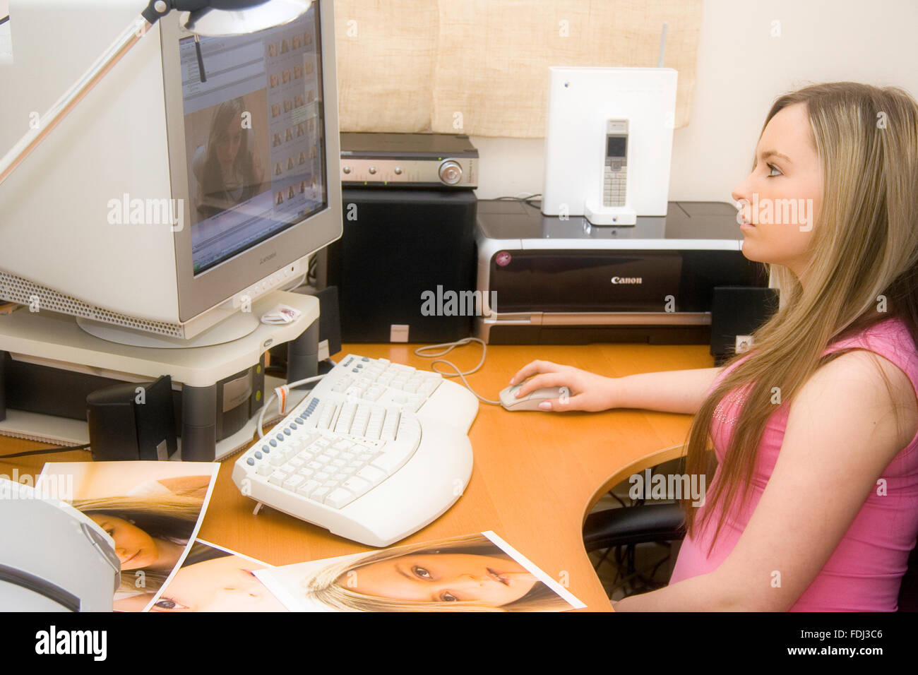 Blonde teenage girl with pink top on, sitting at computer desk looking at CTR monitor while using mouse. Photos Stock Photo