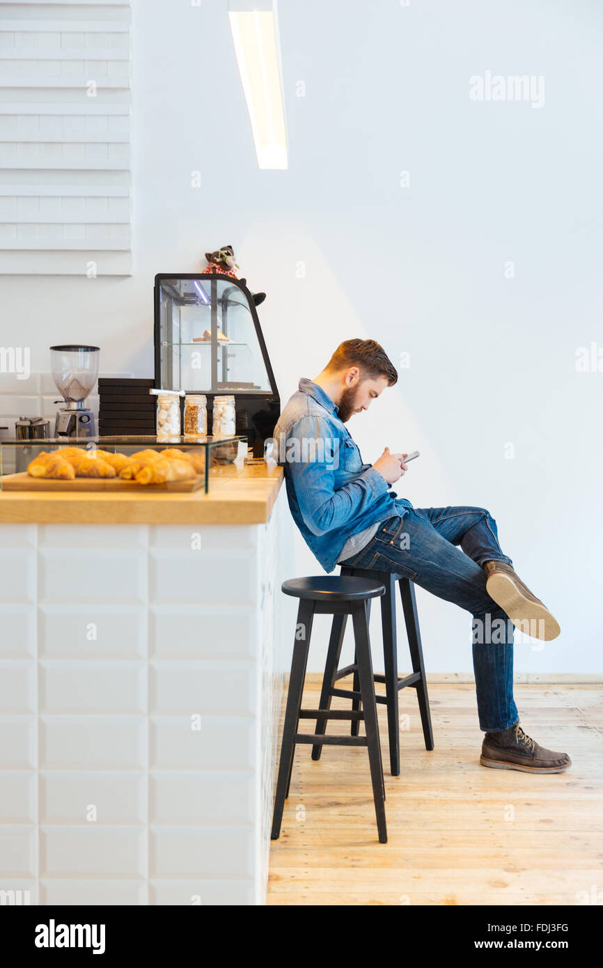 Casual young man using smartphone in cafe - Stock Image
