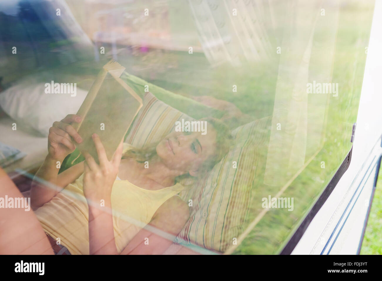 Beautiful woman in a camper van - Stock Image