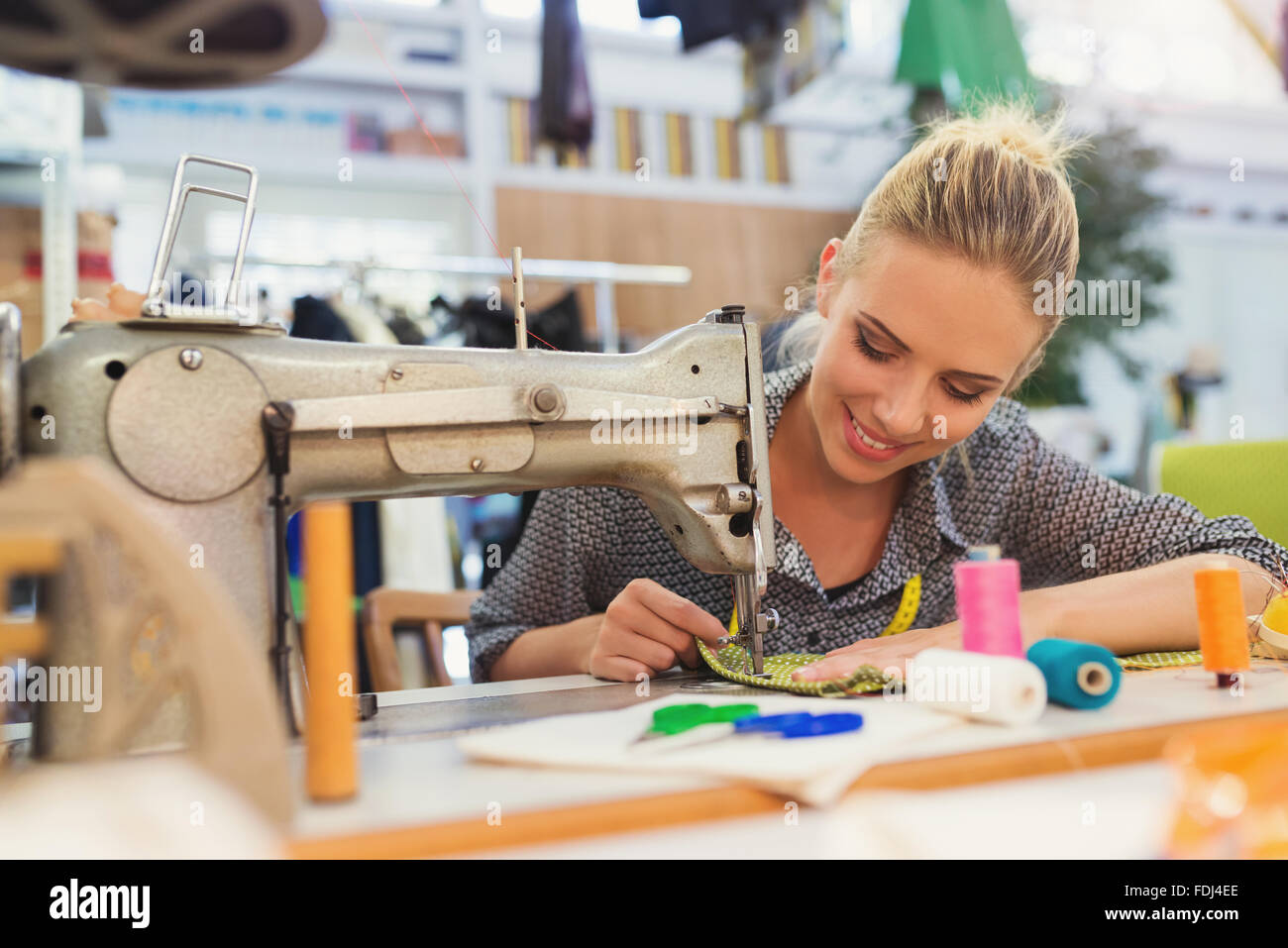 Young woman with sewing machine - Stock Image