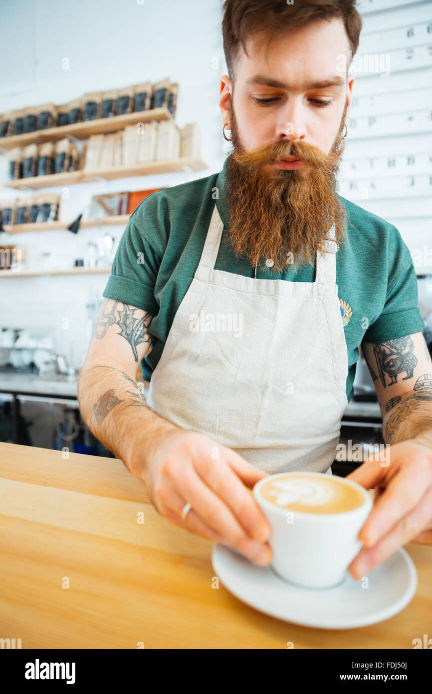 Handsome man preparing coffee in coffee shop - Stock Image
