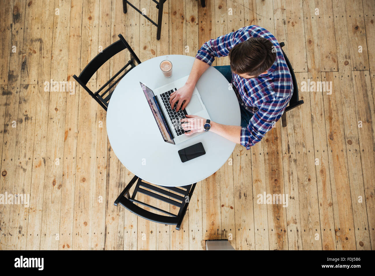 Top view portrait of a man using laptop computer in cafe - Stock Image