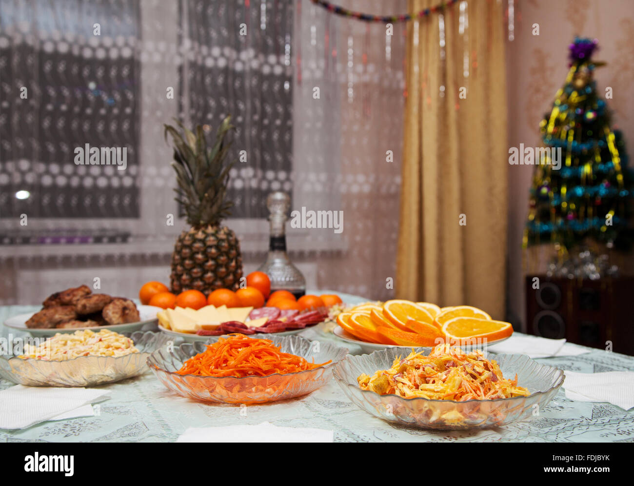 festively laid table with salads, pineapple and  tangerines - Stock Image