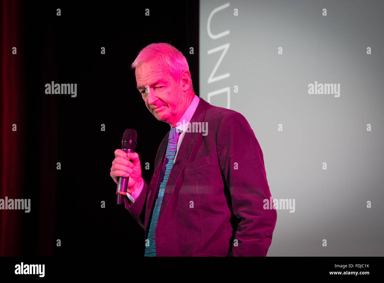 English Journalist and New presenter Jon Snow holding a microphone, lit in electric neon colour. - Stock Image