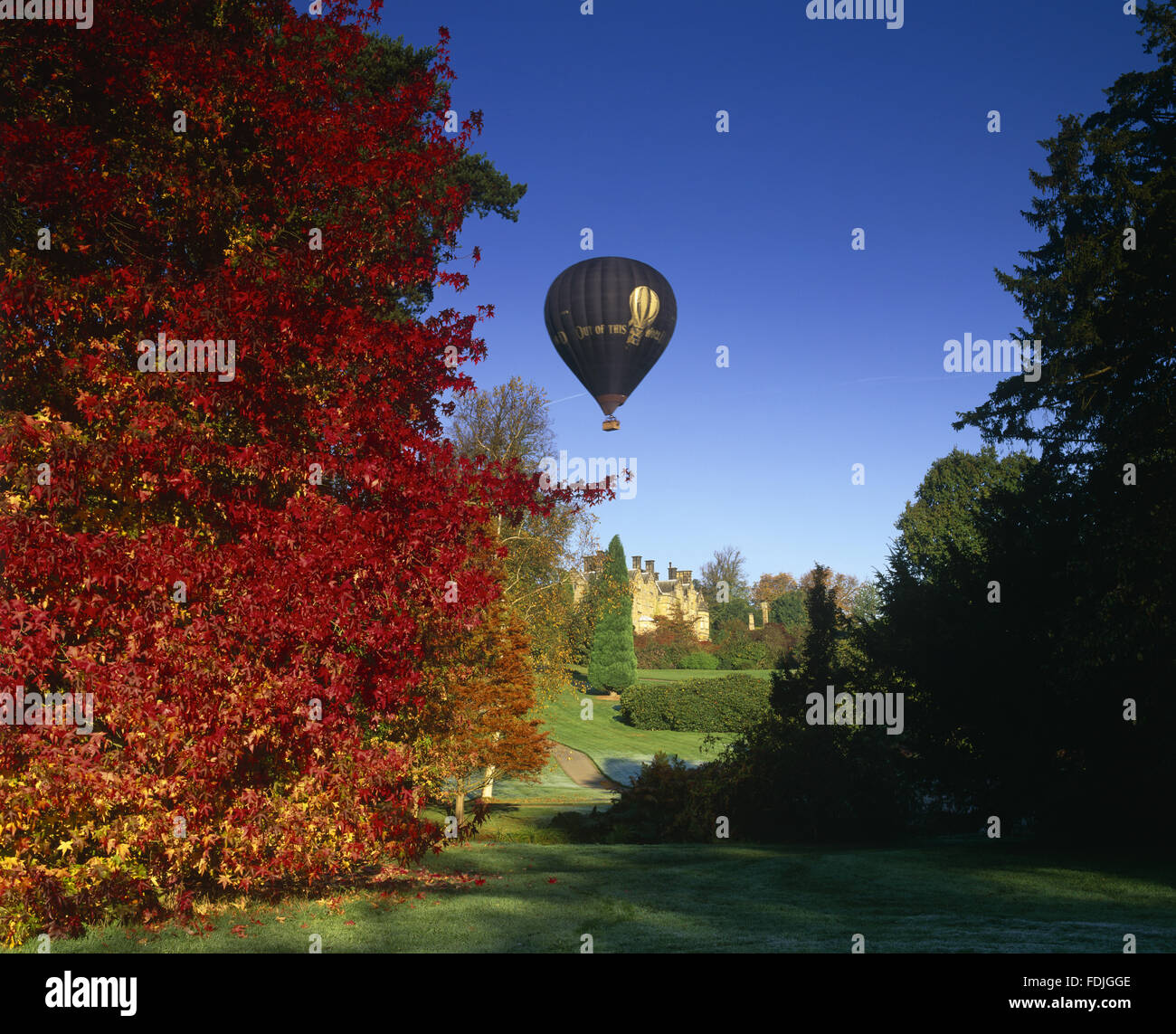 A hot air balloon glides over the Victorian house at Scotney Castle, Lamberhurst, Kent. - Stock Image