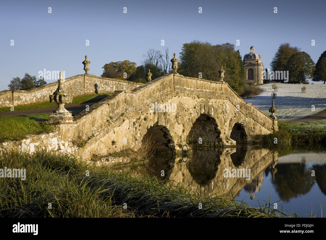 The Oxford Bridge with urns and rustic stonework on a frosty day at Stowe Landscape Gardens, Buckinghamshire. Stock Photo