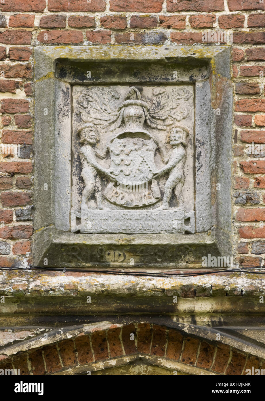 A stone sculptural panel with a coat of arms flanked by attendant figures. - Stock Image