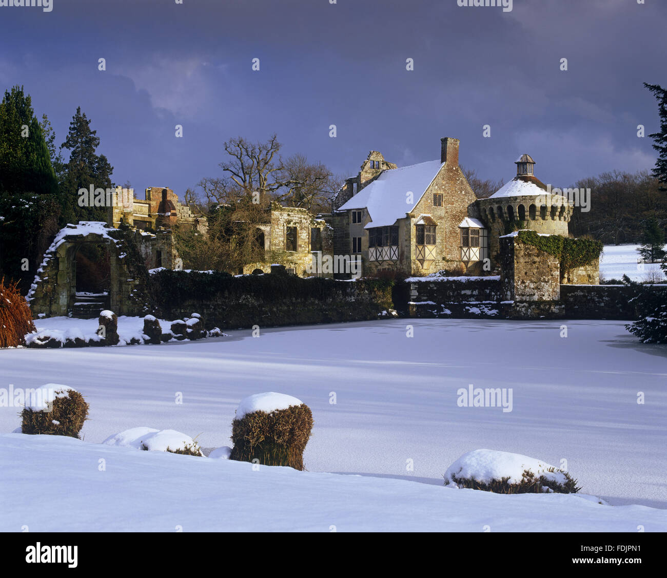 The picturesque fourteenth-century ruined castle in winter, under a heavy snow at Scotney Castle, Lamberhusrt, Kent. - Stock Image